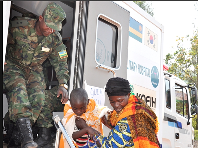 Mother helps child walk down from Rwanda military hospital Mobile medical van.