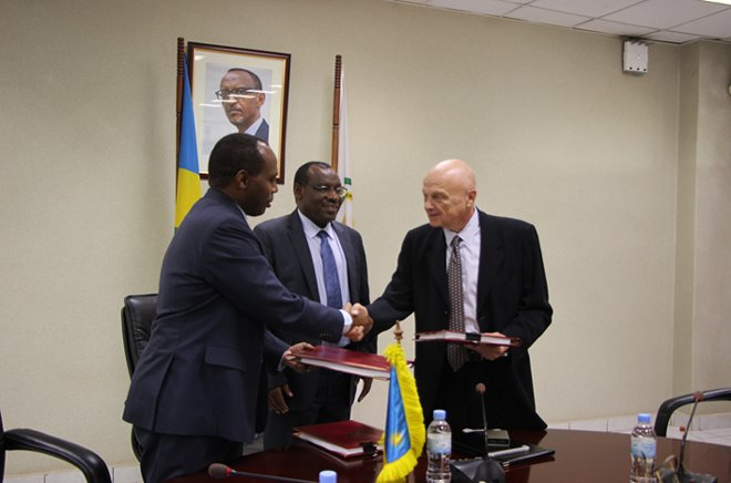 (r) Oshens Group representative Alexis Lifschtz shakes hands with Francis Gatare(l) of RDB as Finance Minister Claver Gatete looks on