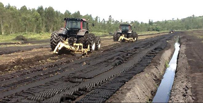 Tractors harvesting peat in remote Rwanda