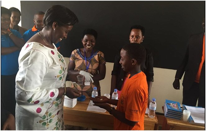First Lady gives de-worming tablet to a student in Nyagatare district at the African child's day anniversary