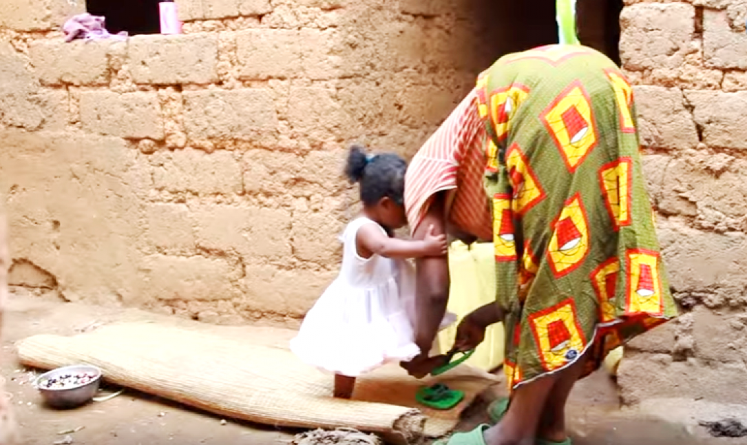 Mother helping daughter to wear shoes