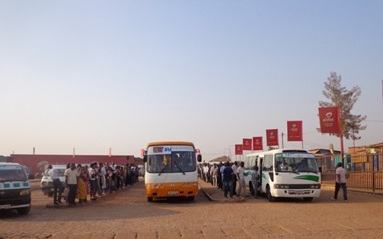 Passengers boarding buses at a bus terminal in Kigali city