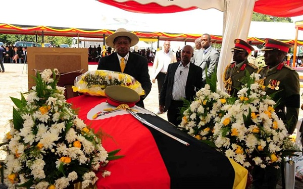 Uganda's president lays a wreath of flowers on the casket of the late General Aronda Nyakairima.