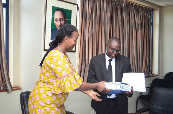 Dr Solange Hakiba, Permenant Secretary at Ministry of Health(Left) hands over CBHI documents to Jonathan Gatera, RSSB Director General today.