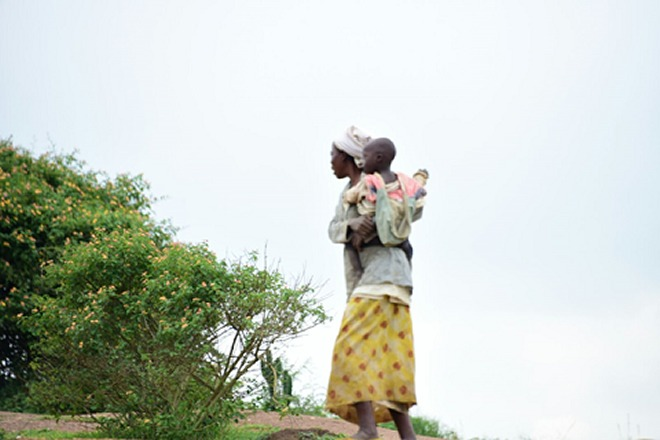 A mother and her baby in Nyagatare district stands on top of a hill to gain a strategic view of the race