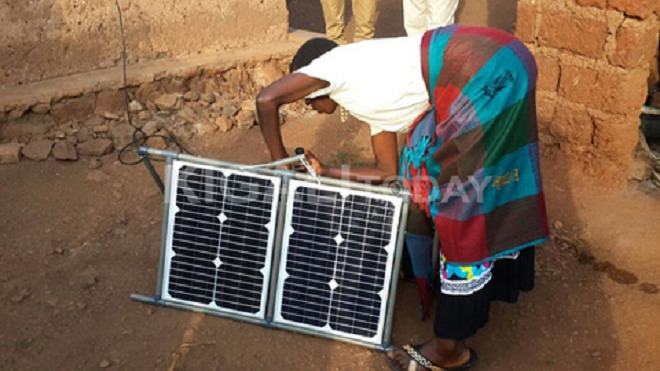 A woman in rural Rwanda tries out a new solar power kit - one of the several power sources which government is encouraging