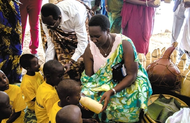 Bernard Makuza the Rwanda Senate President feeding children with milk during the national Umuganura day -a traditional cultural event that used to bring communities together to share seasonal agricultural produce