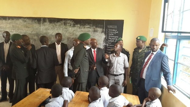 Pupils in class look on as Minister Kaboneka and RDF officials discuss