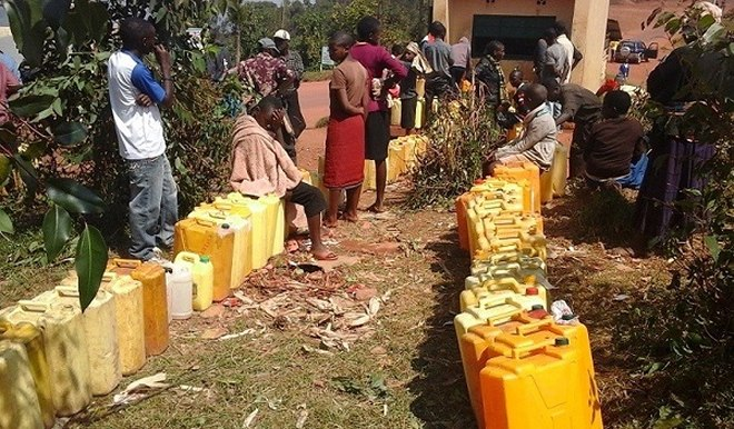 Residents queue to fetch water at a public tap