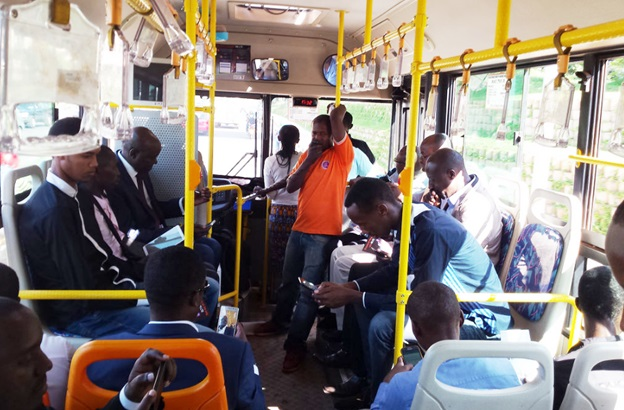 Passengers browsing internet on their gadgets in transit aboard Rwanda's public transport buses fitted with 4GLTE internet.