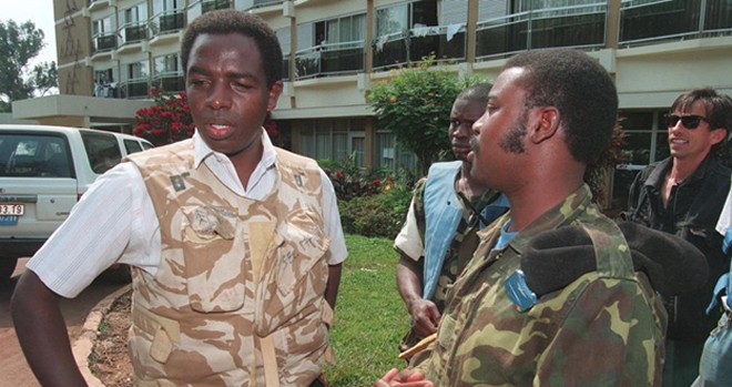 Father Wenscelas Munyeshyaka(L) surrounded by Rwandan soldiers, the ex-far