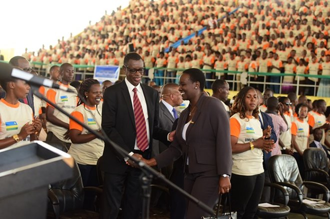 Rwanda's defence minister Gen. James Kabarebe shakes hands with Julienne Uwacu Minister for Sports and Culture