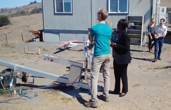 Louise Mushikiwabo (r) guided as she launches drone at Zipline Facility in California