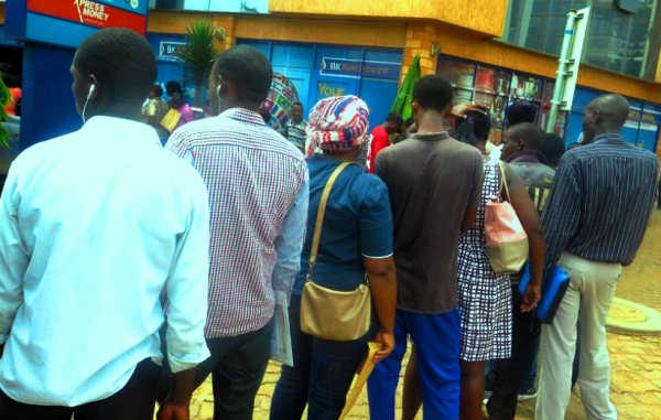 Clients queue outside a bank waiting to be served despite surge of ATMs