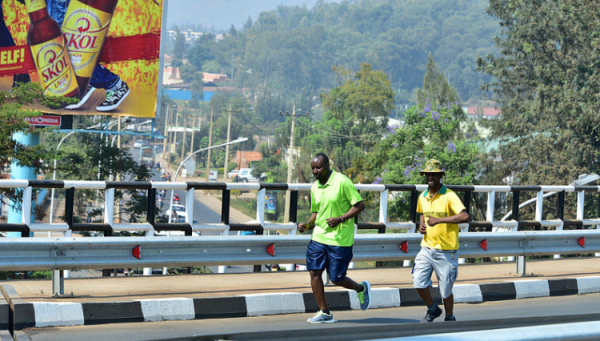 Kigali residents Jogging past an old billboard