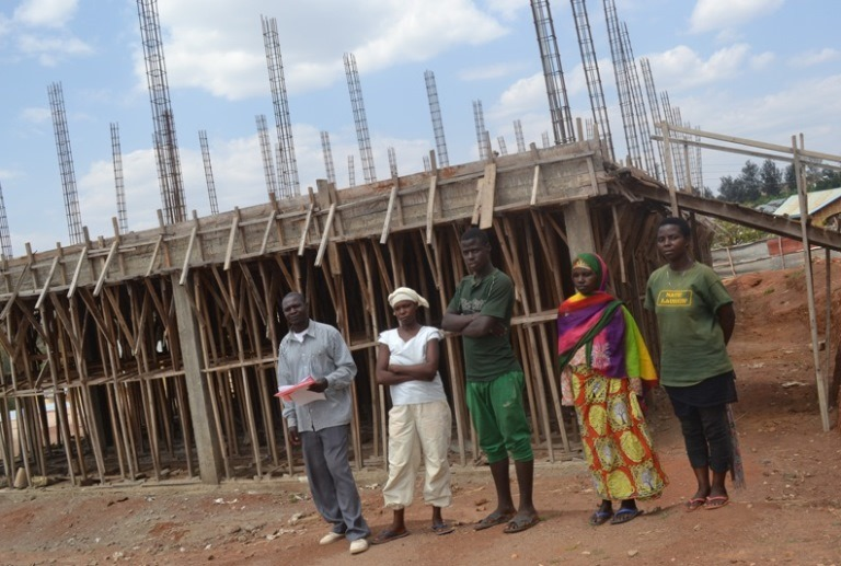 1-workers-stand-in-front-of-the-stalled-ngarama-hospital-the-contractor-owed-workers-rwf-100-million-in-arrears